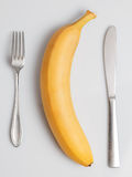 Banana with fork and knife. Banana with a fork and knife on a wooden table Royalty Free Stock Image