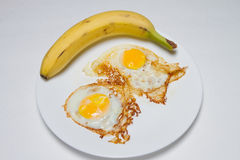 Banana fried eggs. Yellow banana with sunny side up fried eggs Royalty Free Stock Photo