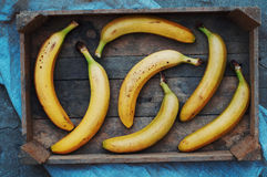 Ripe yellow bananas in wicker basket, on wooden background, view from above, yellow fruits, yellow bananas in a wooden box, food,  Stock Photo