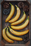 Ripe yellow bananas in wicker basket, on wooden background, view from above, yellow fruits, yellow bananas in a wooden box, food,  Stock Photography