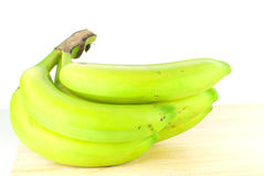 Banana fruit. Tropical green banana fruit on wooden base and white background Royalty Free Stock Photography
