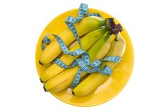 Banana fruits and measuring tape on the plate Royalty Free Stock Photos