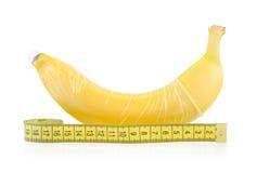 Banana gialla con il preservativo e nastro adesivo di misurazione Fotografie Stock Libere da Diritti