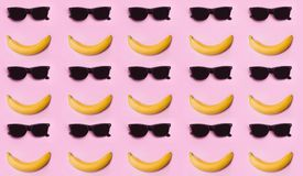Banana and glasses. Sunglasses. Summer. The sun. Smile. The face is laid out with a banana and glasses. Pink background. Pink Lavender Royalty Free Stock Photography