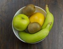 Banana grapefruit kiwi Apple in a bowl of fresh juicy tropical exotic vitamins on a wood Royalty Free Stock Photo