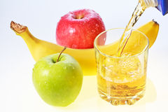 Banana, green and red apples and glass of juice Stock Photos