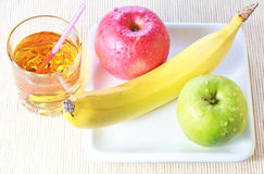 Banana, green and red apples and glass of juice Royalty Free Stock Photos