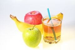 Banana, green and red apples and glass of juice Stock Image