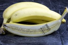 Banana cut in half with nutrition label on black marble Royalty Free Stock Photography