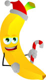 Banana holding a candy cane and wearing Santa's hat Royalty Free Stock Photo