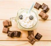 Banana i kiwi milkshake w kamieniarza słoju z creme na słomie dekorował z czekoladą i czarnymi jagodami Mieszkanie nieatutowy wie Zdjęcie Stock