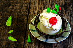 Banana ice cream with cherry in cup Stock Image