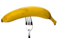 Banana impaled on a fork on a white background Stock Photos