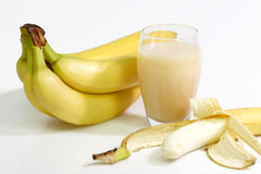 Banana Juice. A glass of banana juice with fres bananas on bright background Royalty Free Stock Images