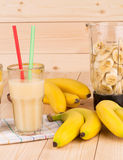 Banana juice and blender full of sliced fruits. Royalty Free Stock Images