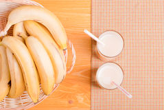 Banana juice in a glass on a yellow napkin on the table next to Royalty Free Stock Image