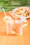 Banana juice in two cups with straws and umbrellas on a yellow t Royalty Free Stock Photography