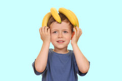 Banana kid. Five years old boy with banana isolated on blue Stock Photography
