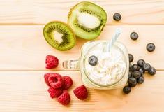 Banana and kiwi milkshake in mason jar with creme on top and drinking straw decorated with fresh raspberries, blueberries and kiwi. Kiwi and banana milkshake in Stock Photo