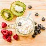 Banana and kiwi milkshake in mason jar with creme on top and drinking straw decorated with fresh raspberries, blueberries and kiwi. Kiwi and banana milkshake in Royalty Free Stock Image