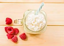 Banana and kiwi milkshake in mason jar with creme on top and drinking straw decorated with fresh raspberries. flat lay top view sm. Kiwi and banana milkshake in Royalty Free Stock Photos