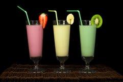 Banana, kiwi and strawberry milk shake and fresh fruis. Cocktail with milk. White isolated glass of milkshake Royalty Free Stock Photos