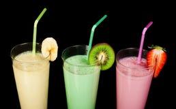 Banana, kiwi and strawberry milk shake and fresh fruis. Cocktail with milk. White isolated glass of milkshake Stock Images