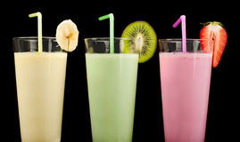 Banana, kiwi and strawberry milk shake and fresh fruis. Cocktail with milk. White isolated glass of milkshake Stock Photo