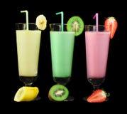 Banana, kiwi and strawberry milk shake and fresh fruis. Cocktail with milk. White isolated glass of milkshake Stock Photography