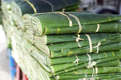Banana leafes at a asian vegetable market. Fresh banana leafes at a fruit and vegetable market in Bangkok, Thailand. Used for packing cooked rice meals Royalty Free Stock Photo