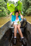 Banana leafs umbrella. Beautiful tourist on a trip in a traditional boat on a river in Masoala national park, Madagascar, with a banana leafs umbrella in the Royalty Free Stock Images