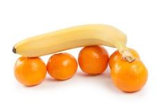 Banana lies on top of the mandarins Stock Photo