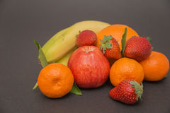 banana, maçã, laranja, morangos e tangerina três com folhas em um fundo cinzento bonito, cores bonitas e compositi Fotografia de Stock