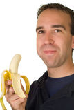 Banana Man. A man chewing a fresh banana, isolated on a white background Royalty Free Stock Images