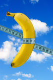 Banana with measure tape on sky background Royalty Free Stock Images