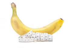 Banana and measuring tape. On a white background Royalty Free Stock Photo