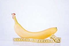 Banana and measuring tape. Banana being measured with measuring tape Royalty Free Stock Image