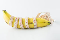 Banana with measuring tape. Yellow banana, with measuring tape indicate male's penis length, or men's health. It also indicate food for fitness & diet Royalty Free Stock Photography