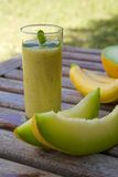Banana-melon smoothie. A glass of banana-melon smoothie. Fresh bananas and green melon in the background Royalty Free Stock Photos