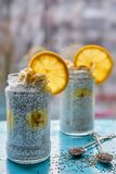 Banana milk pudding with chia and orange in glass jars decorated with two spoons with raw chia seeds on blue wooden board Stock Photo