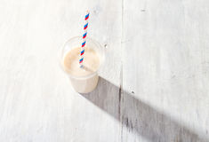 Banana milkshake in plastic cup on white wooden background stock images