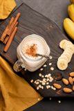 Banana milkshake or protein smoothie drink with cinnamon and oats. Top view, selective focus royalty free stock photos