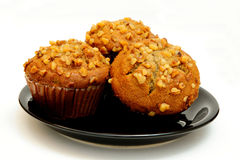 Banana Muffin. Closeup of three banana nut muffins topped with crushed walnuts on a black saucer with a light colored background Royalty Free Stock Photo