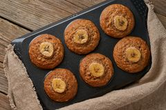Banana muffin  in tray, top view. Cupcakes on old linen napkin, rustic wooden table, a breakfast with cake stock photography