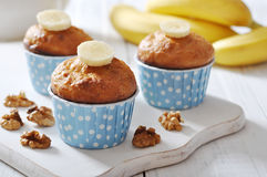 Banana muffins in blue paper cupcake case. With nuts over wooden background Royalty Free Stock Photography