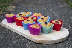 Banana muffins with chocolate, blackberries, strawberries, nuts and raisins in silicone molds on wooden mat, colorful hearts royalty free stock photos