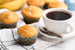 Banana muffins and cup of coffee. Banana muffins with oat flakes and cup of coffee on white table, closeup view stock images