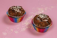 Banana muffins sprinkled with sesame in rainbow colored baking cups on pink background. stock photo