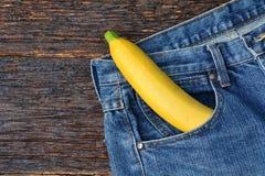 Banana no saco de calças de brim textura da sarja de Nimes, calças de brim da sarja de Nimes na parte traseira de madeira Imagens de Stock Royalty Free
