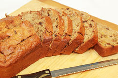 Banana Nut Bread. Oven fresh home baked loaf of banana nut bread sliced ready for serving on a wooden tray board Stock Photo